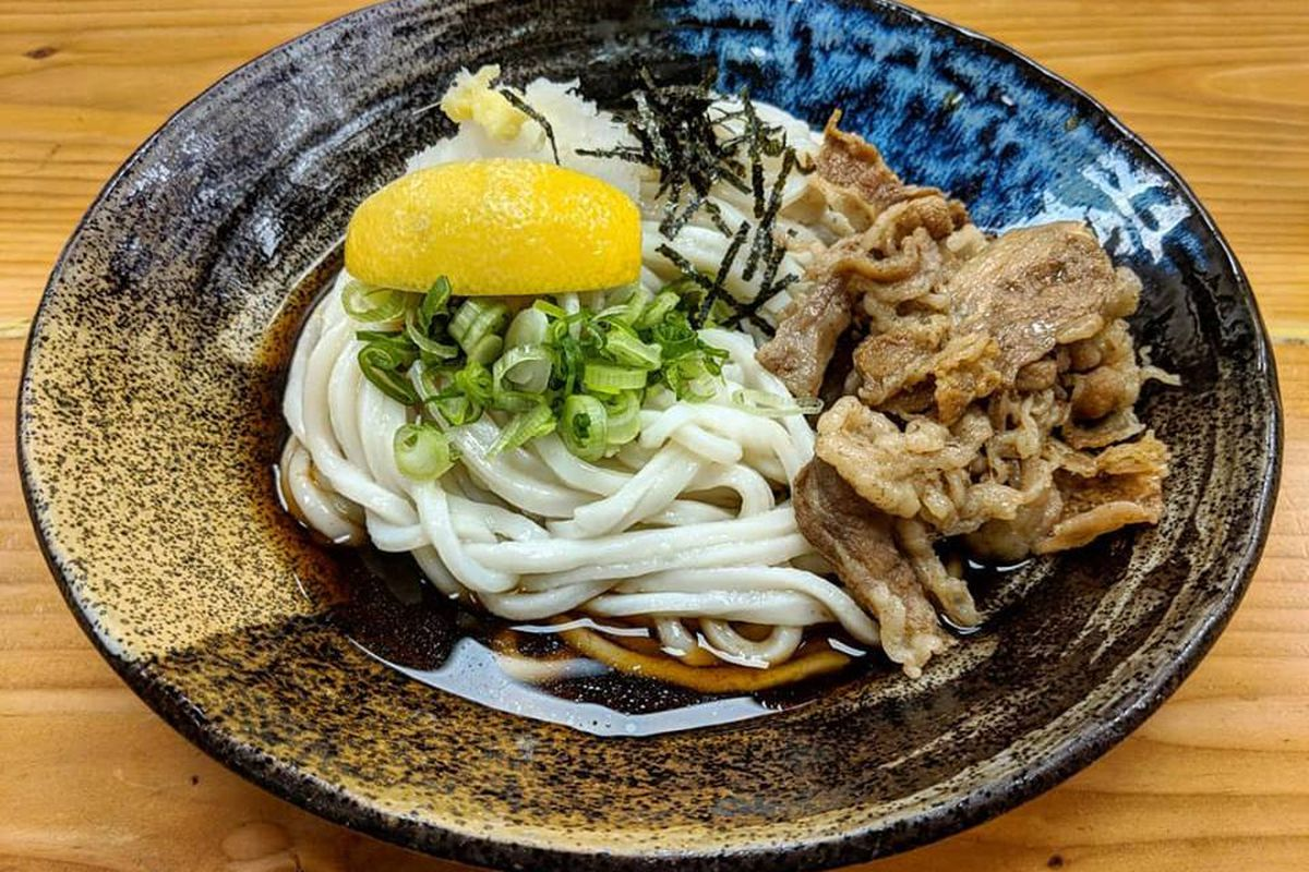 A black bowl that has an artistic, handmade look is full of udon and thinly sliced beef in a thin brown broth. The udon is topped with chopped scallions, slivers of seaweed, and a lemon wedge. The bowl sits on a light wooden table.
