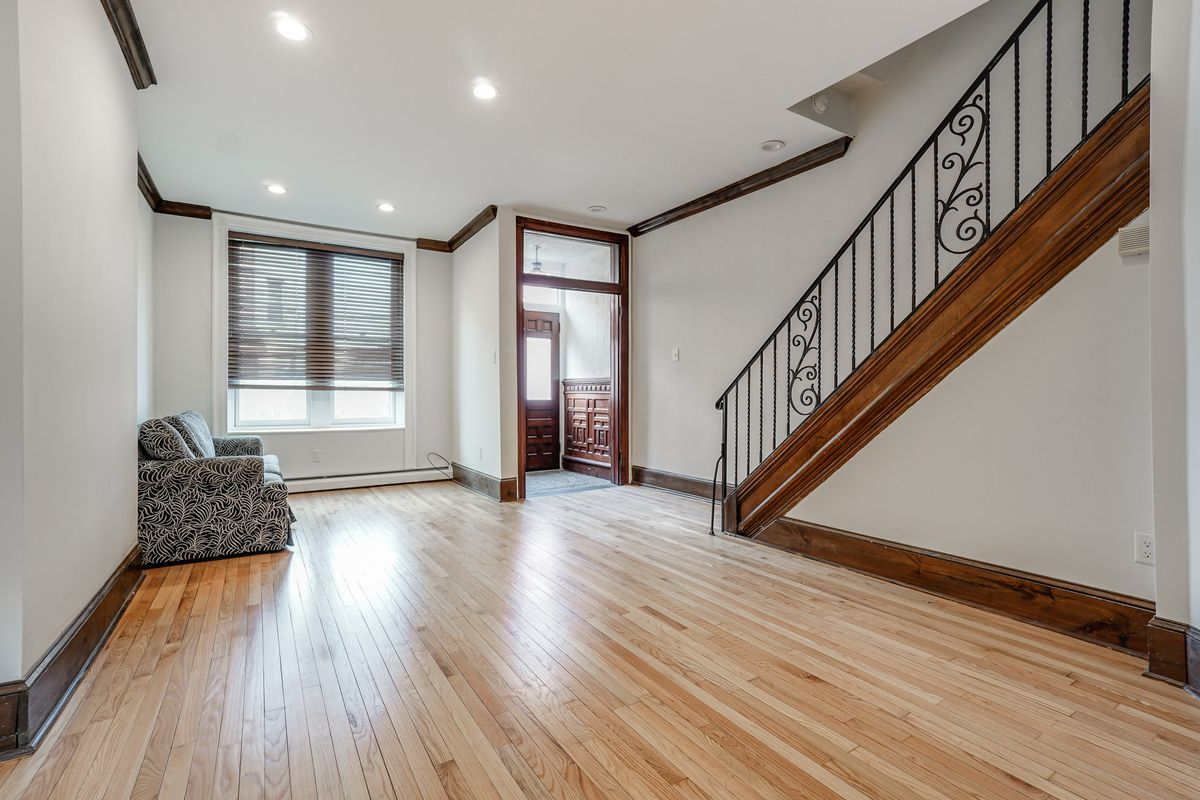 A living room with refinished hardwood floors and a foyer.