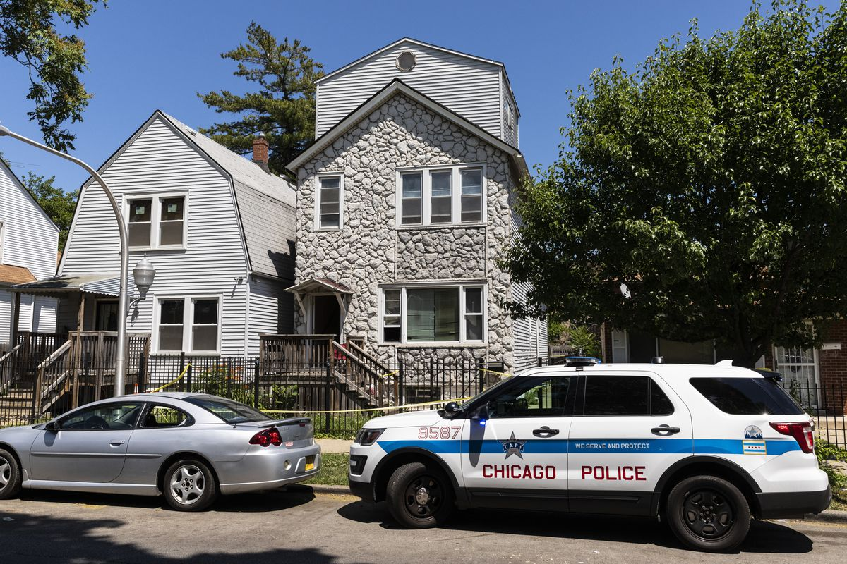 Chicago police keep watch and crime scene tape hangs outside a house in the 6200 block of South Morgan, where eight people were shot, four fatally, inside the Englewood building, Tuesday afternoon, June 15, 2021.