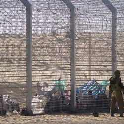 African refugees sit on the ground behind a border fence after they attempted to cross illegally from Egypt into Israel as Israeli soldiers stand guard near the border with Egypt, in southern Israel, Tuesday, Sept. 4, 2012. Israel is staunching the flow of African migrants who have poured into the Jewish state by the tens of thousands, rapidly building a border fence and implementing a new policy of detaining Africans upon arrival. Israel's army says over the past few days, a group of African migrants has waited on the Egyptian side of the fence. Israeli soldiers are providing the group with water, but not allowing them into Israel.