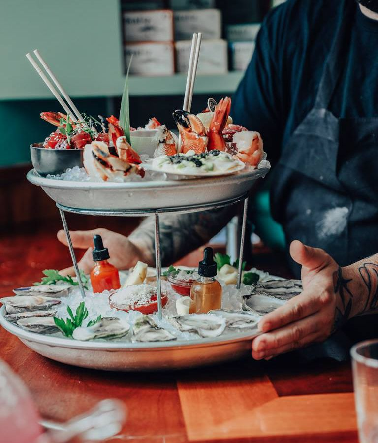 Two platters of raw bar items on ice sit on a metal stand atop each other