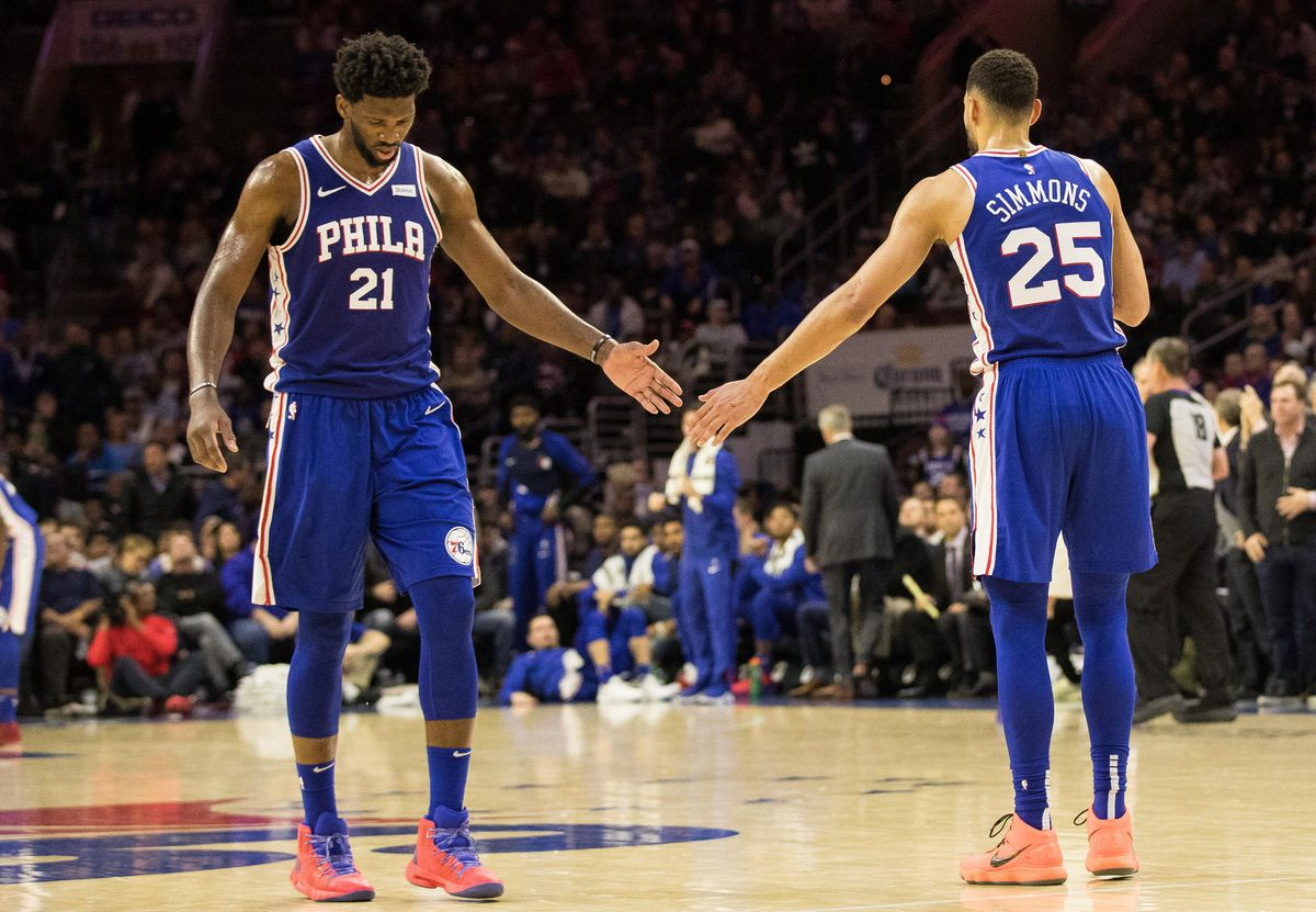 Joel Embiid high-fives Ben Simmons on the court