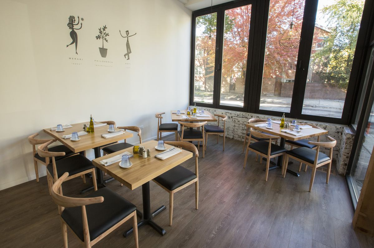 A white dining space with two wooden two-top tables and chairs, beside large bi-fold windows.