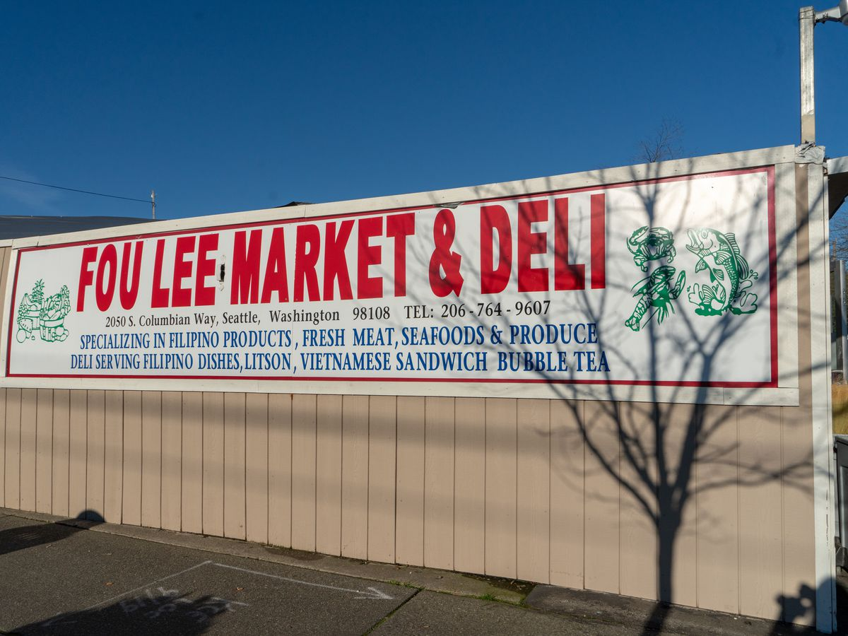 The sign outside Fou Lee Market & Deli with the grocery's name in bold red letters.