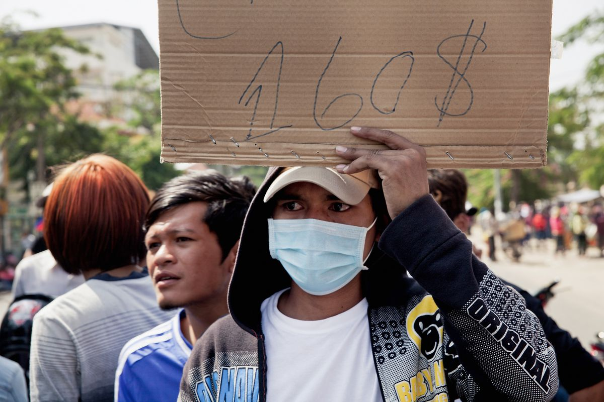 A garment worker on strike holds a banner demanding a minimum salary of $160 a month on December 27, 2013, in Phnom Penh, Cambodia.