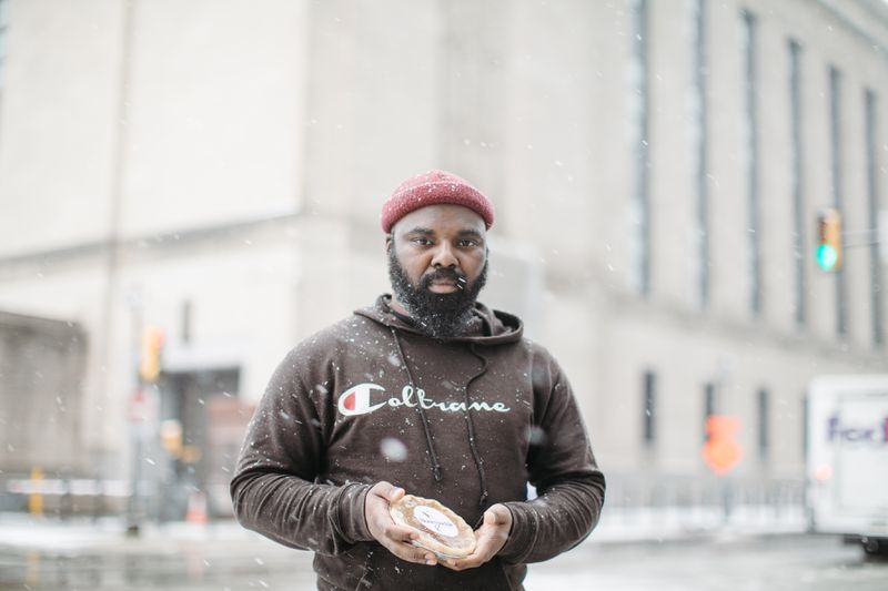 A man stands in the snow on a street corner holding a small pie