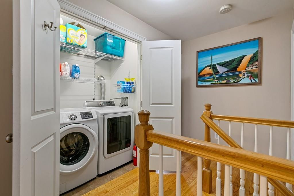The top of a stairwell with an opened closet with washer-dryer side by side in it.