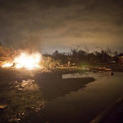 """A fire burns in the Pinaire mobile home park in Wichita, Kansas after a tornado caused massive destruction in the area on Saturday night April 14, 2012. Tornadoes were spotted across the Midwest and Plains on Saturday as an outbreak of unusually strong weather seized the region, and forecasters sternly warned that """"life-threatening"""" weather could intensify overnight."""