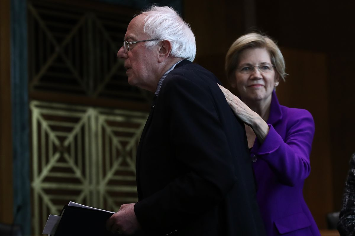 Sen. Elizabeth Warren (R) (D-MA) pats Sen. Bernie Sanders (L) (I-VT) on the back.