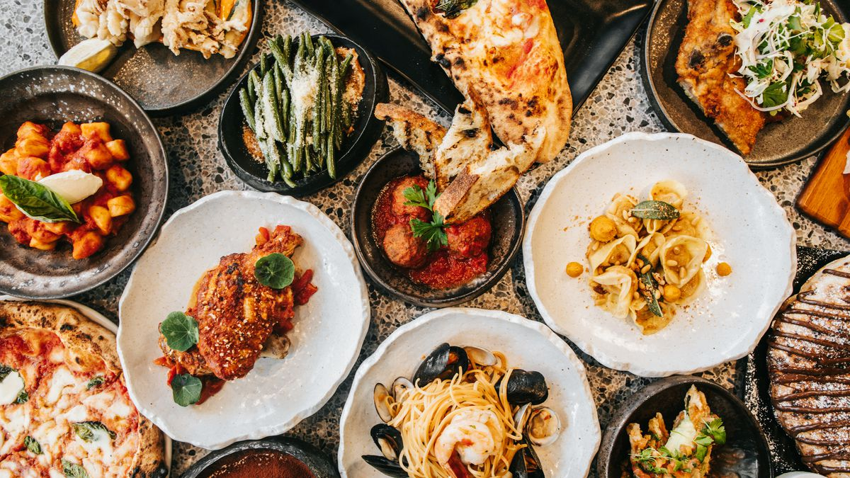 A table with pasta, pizza, bread, and vegetables