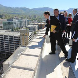 Gov. Gary Herbert, joined by local business leaders and other elected officials, looks over the edge of the Walker Center in Salt Lake City on Tuesday, May 3, 2016. The group was there to discuss Downtown Rising projects and its priorities for the next 10 years.