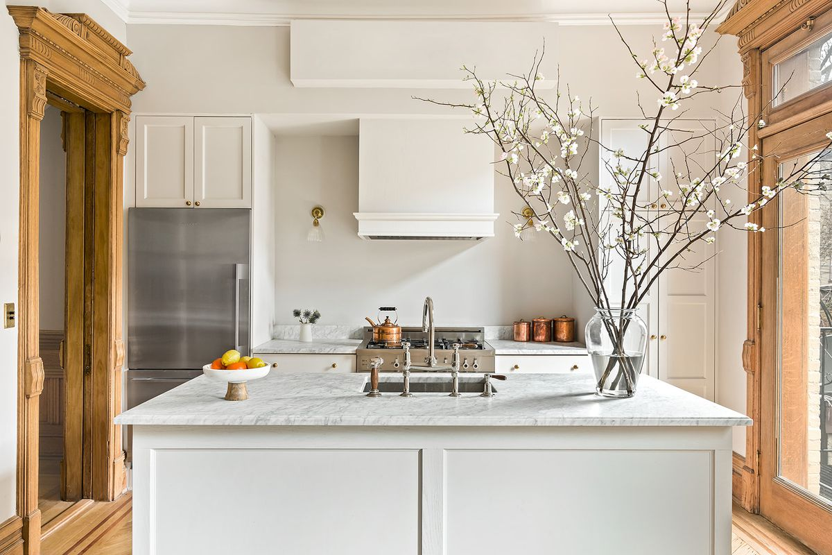 The kitchen features white cabinetry including a center island, white marble countertops, and stainless steel appliances flanked by pale oak moldings.