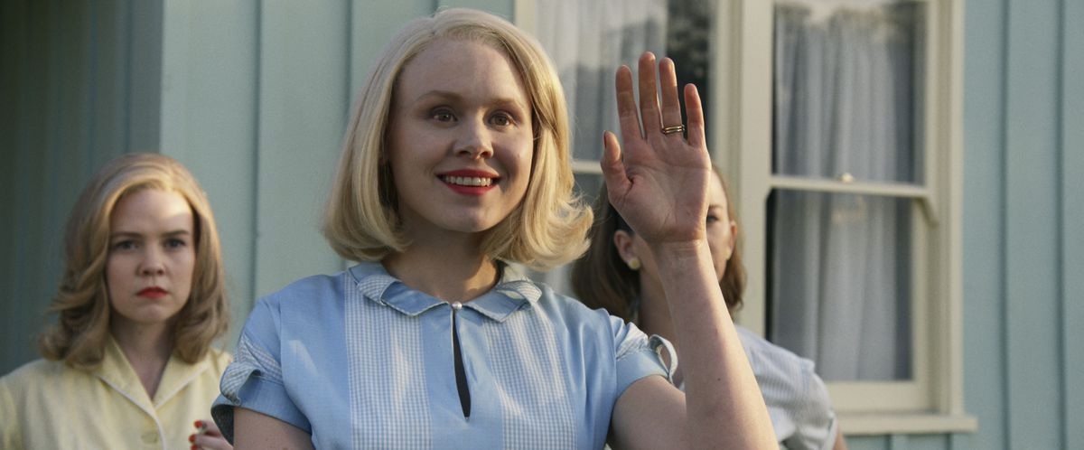 Alison Pill waves with a stiff smile in Amazon Studios' Them