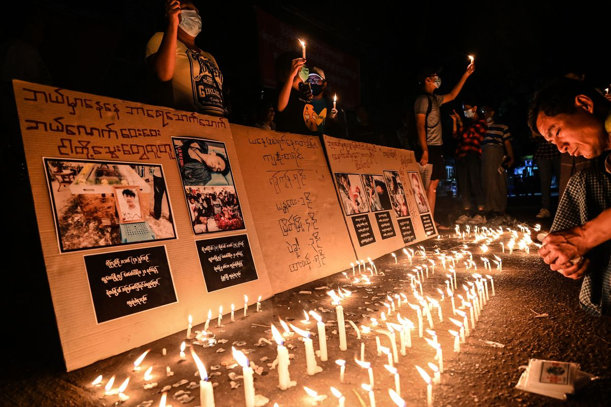 Lines of lit candles illuminate a row of cardboard signs featuring photos and handwritten text. Protesters standing behind the signs in masks hold more candles, and in front of them, a man kneels with his head bowed.