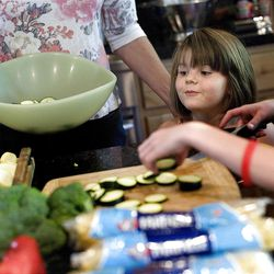 Ella Udell, 5, watches her mothers and sister cut up vegetables for a pasta primavera salad that was to be donated to the OccupySLC demonstrators who are camped at Pioneer Park on Thursday, October 12, 2011.