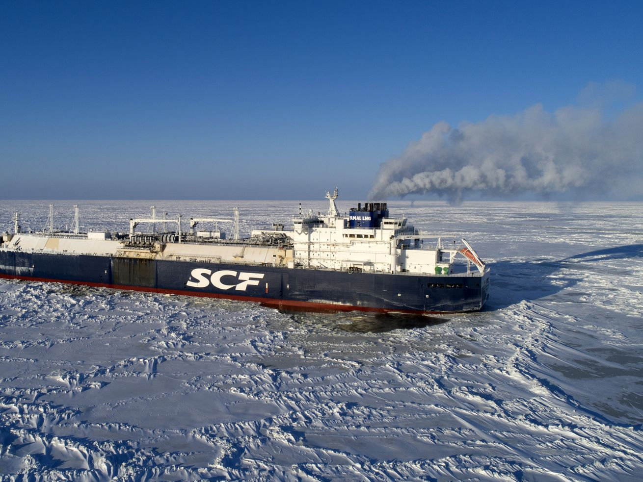 A large blue and white commercial ship belching smoke travels across sea ice in the middle of winter.
