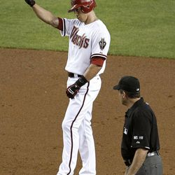 Arizona Diamondbacks' Cody Ransom acknowledges the team in the dugout after his two-run double against the Philadelphia Phillies, as umpire Ed Rapuano watches during the second inning of a baseball game Monday, April 23, 2012, in Phoenix.