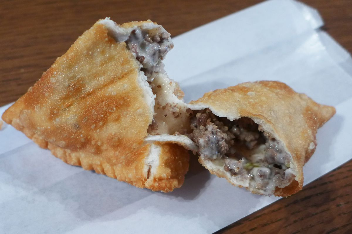 An empanada twisted to show the ground meat and cheese inside.