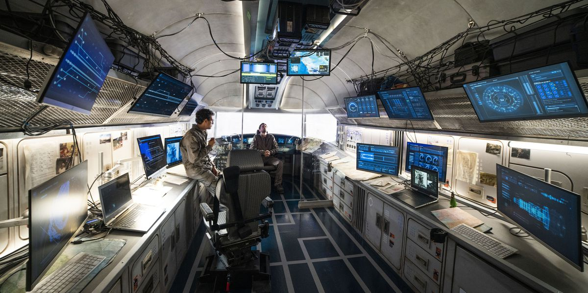 Two people in drab jumpsuits at the far back of a grungy beige space full of monitors showing statistics and diagrams.