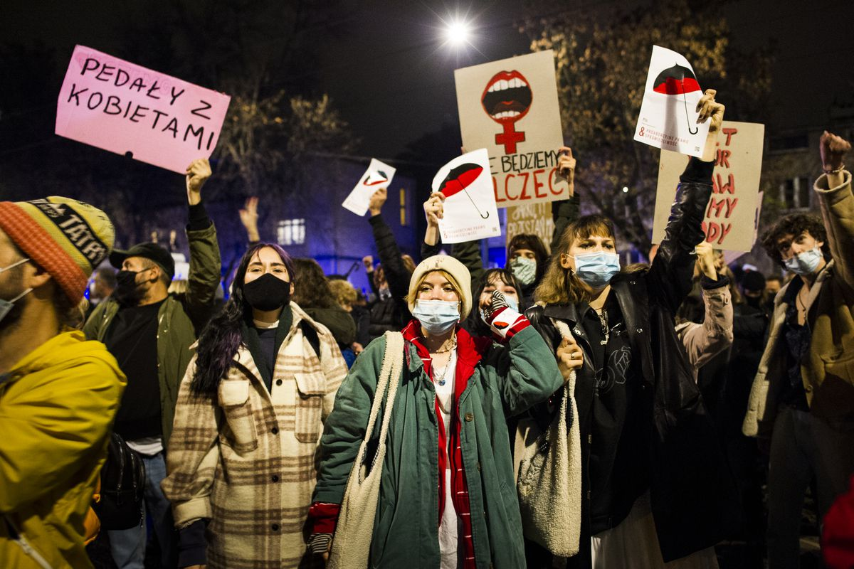 "A group of largely women, in winter coats and masks, illuminated by the camera's flash, hold signs; one with a red umbrella on white; another with an open mouth atop a cross; another with a message reading ""Pedaly Z Kobietami."" The group is clustered together, and appear to be shouting underneath their masks."