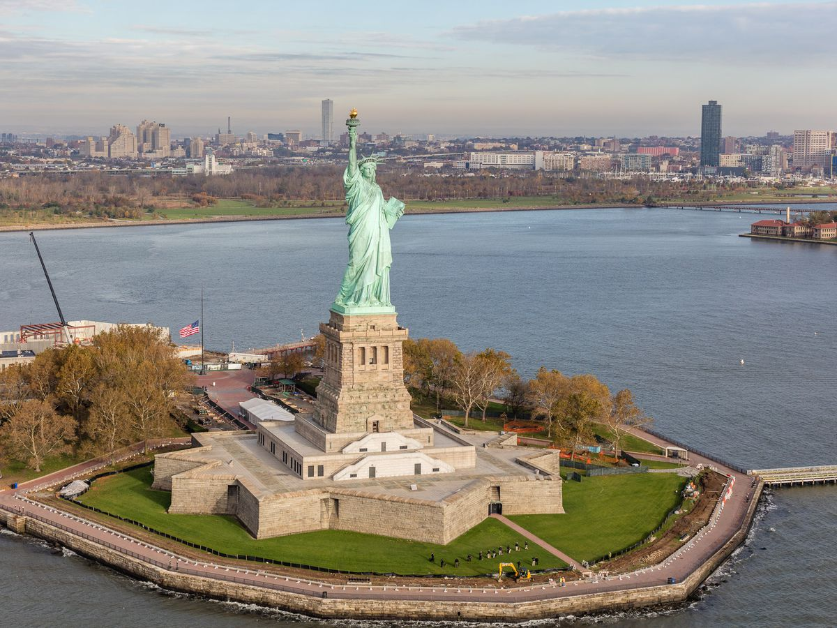 An aerial view of the Statue of Liberty which is a large monument of a woman dressed in robes raising her hand carrying a torch above her head.