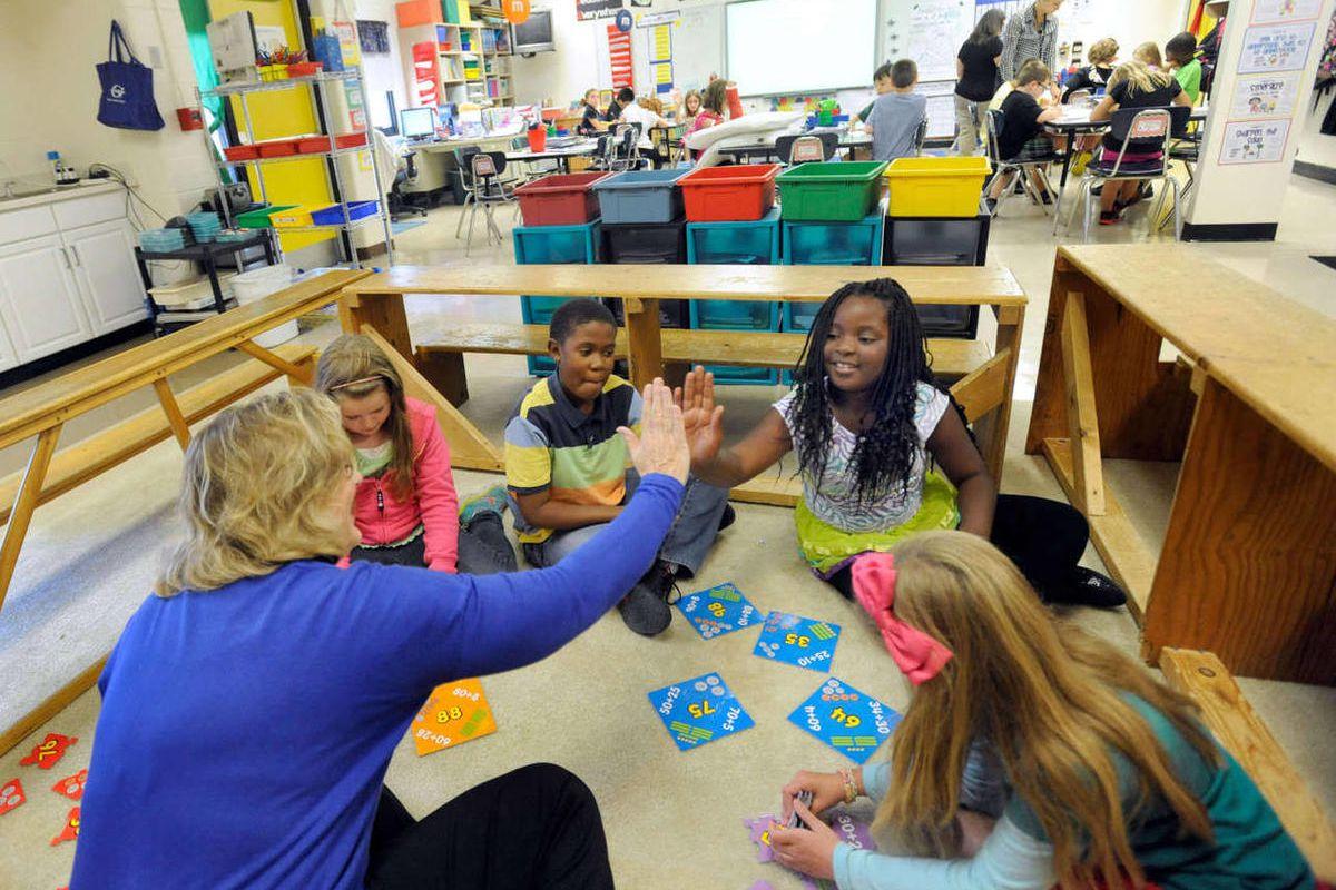 A hird-grade teacher, left, high-fives a student during a math lesson, Tuesday, Oct. 1, 2013.