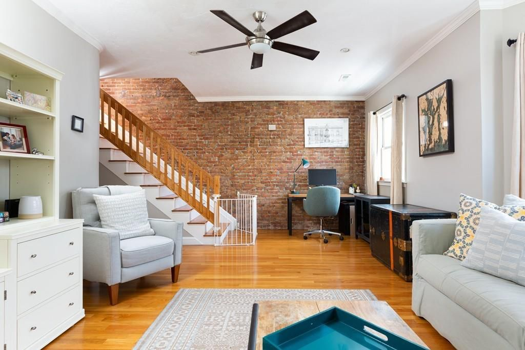 A sizable living room with furniture and a staircase leading up at one end.