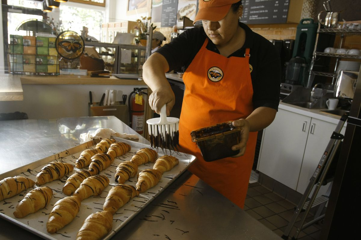 Bernice Ornelas, a manager and cook at La Monarca Bakery, adds topping to chocolate croissants at t