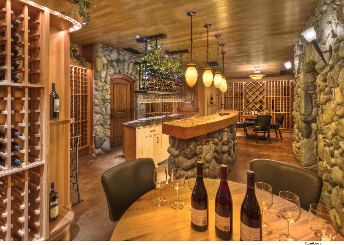 A wine cave with wine racks, seating for tastings, and river rock.