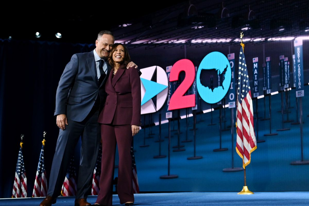 """Douglas Emhoff with his arm around Kamala Harris, in front of a backdrop that says """"2020."""""""