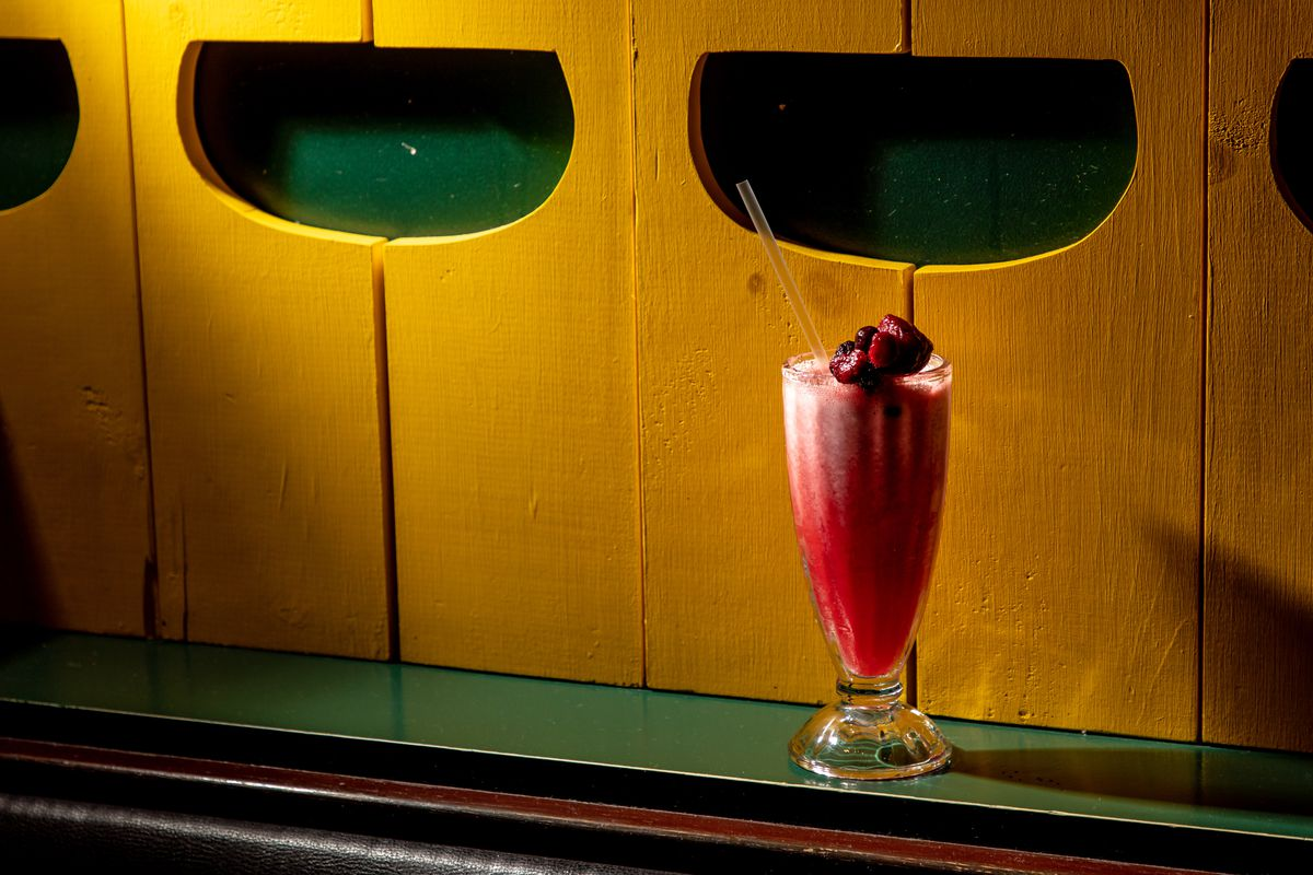 A red and white fruit shake sits on green counter near a yellow wall