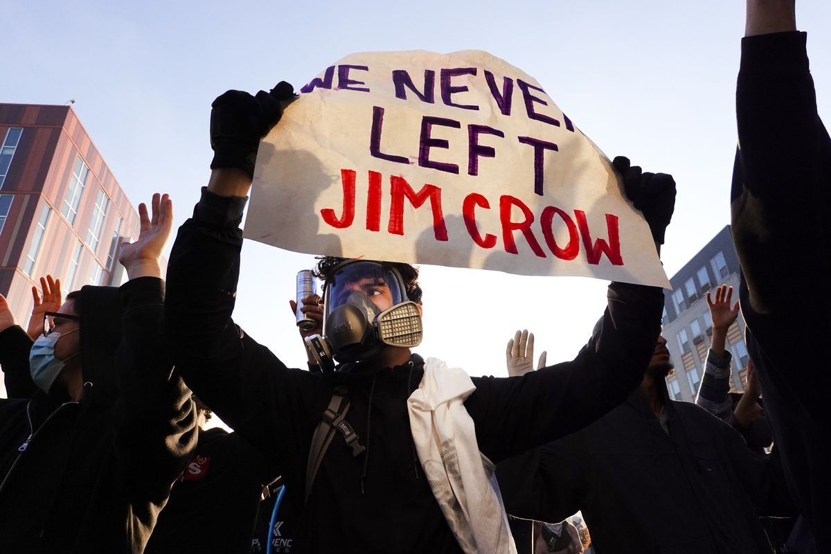 "A man wearing a respirator mask holds a sign reading, ""We never left Jim Crow."""