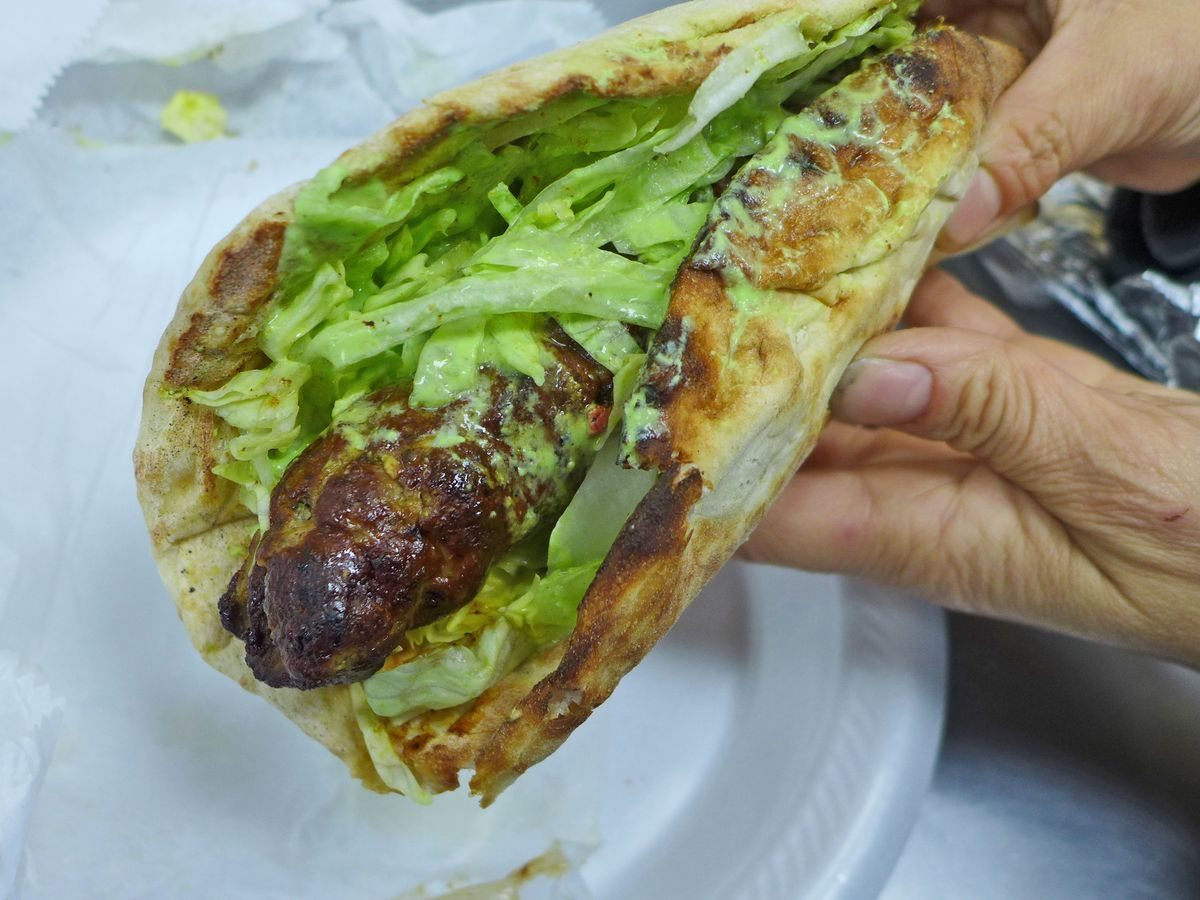 A charred ground lamb kebab bedded in lettuce sticks out of the end of a flatbread.
