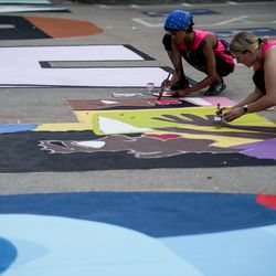 Katlyn Addison and Kathryn Richards assist in putting the final touches on one of two letters by lead artist Liz Lambson on a Black Lives Matter mural outside of the City-County Building in Salt Lake City on Tuesday, Aug. 4, 2020.