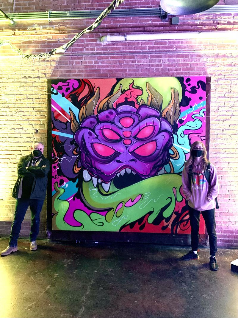 """Brian Keller (left) with his son and helper Bryson (right) in front of the mural Keller created for Artopia, titled """"Cosmic Soul Crusher."""""""
