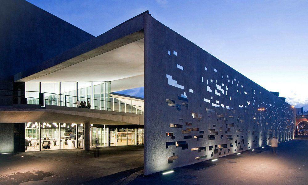 The exterior of the Tenerife Space of Arts.  The facade has shapes cut out which let in light.