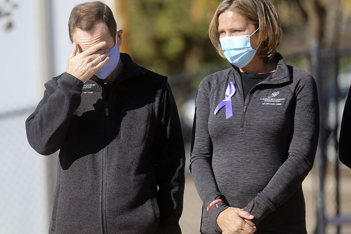 Matt McCluskey, left, wipes his eyes as he and his wife, Jill, listen to a speaker on the two-year anniversary of their daughter Lauren McCluskey's death at the McCarthey Family Track and Field Complex in Salt Lake City on Thursday, Oct. 22, 2020. Lauren McCluskey, a track athlete, was was shot and killed on campus near her dorm by Melvin Shawn Rowland, 37, after weeks of being stalked and harassed by Rowland.