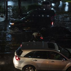 A man pushes a car through a flooded street in Brooklyn.