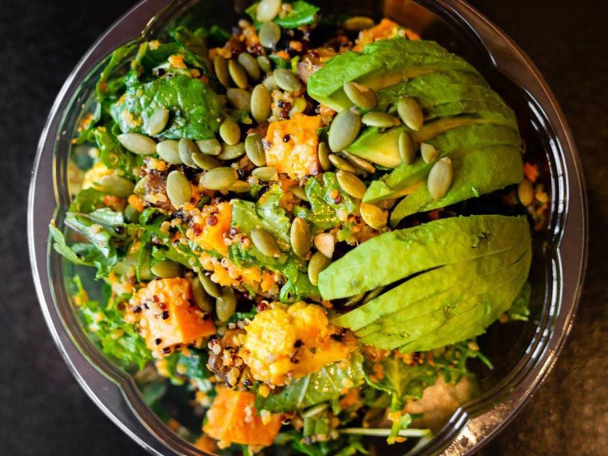 A salad topped with avocado slices, sweet potatoes, and pepitas