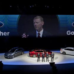 """New Ford Mondeo models seen in the background as Raj Nair, group vice President global product development, left, Alan Mulally, President and CEO of Ford Motor Company, center and on screen, Stephen Odel, chairman and CEO Ford Europe, and Jim Farley, group vice President global marketing, sales & service, from left to right, answer questions during a presentation of fresh Ford models in Amsterdam, Netherlands, Thursday Sept. 6, 2012. Ford has unveiled 15 new or restyled vehicles for the European market that it will launch over five years to revive sales. The refreshed lineup announced Thursday includes a second-generation Kuga midsize SUV to be launched this year, as well as a new Ecosport compact SUV and the European launch of the larger Edge. Ford also will launch the iconic Mustang in Europe. Ford Europe CEO Stephen Odell said improvements in the """"brutal"""" European market are not expected soon. Ford, he said, is increasing its investment in Europe to be ready when the market bounces back."""