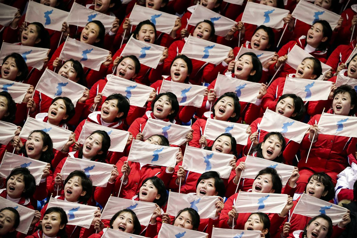 February 10: North Korean supporters hold up the Korean unification flags during the ladies' 500 meters short-track speed skating competition during the 2018 Winter Olympics in Gangneung, South Korea. (Julie Jacobson/AP)