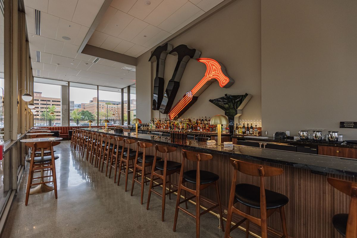 The neon Hammer & Nail sign hangs on the wall behind an extremely long, black bar with mid-century wooden bar chairs and wood beadboard paneling on a slightly cloudy day.