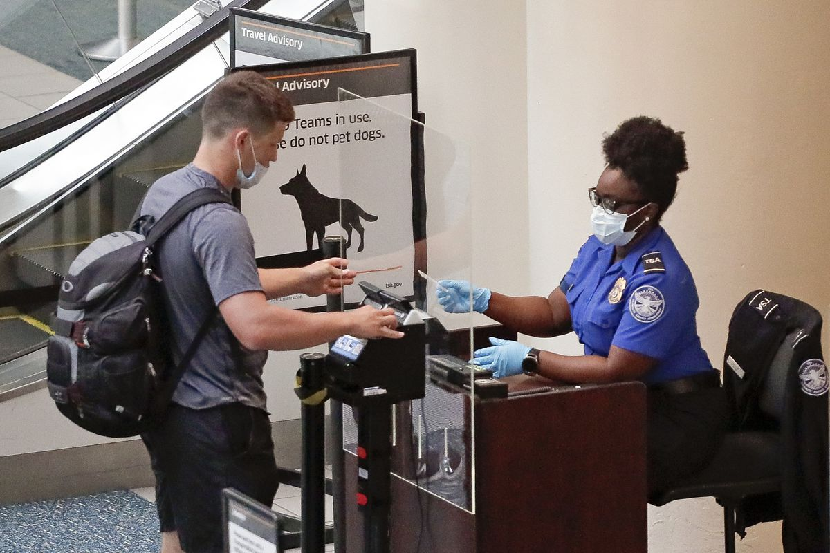 In this June 17, 2020 file photo, a TSA worker, right, checks a passenger before entering a security screening at Orlando International Airport in Orlando, Fla.