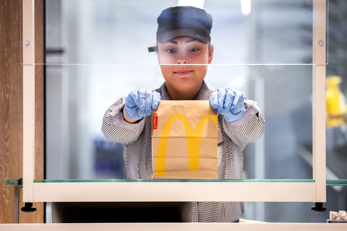 A McDonald's worker behind perspex in the Netherlands