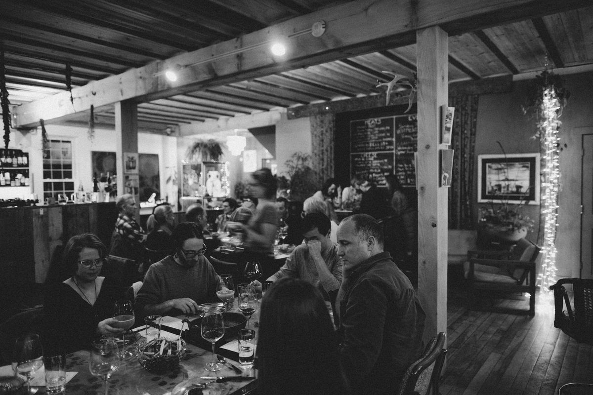 Black and white view of a rustic restaurant interior, full of people eating