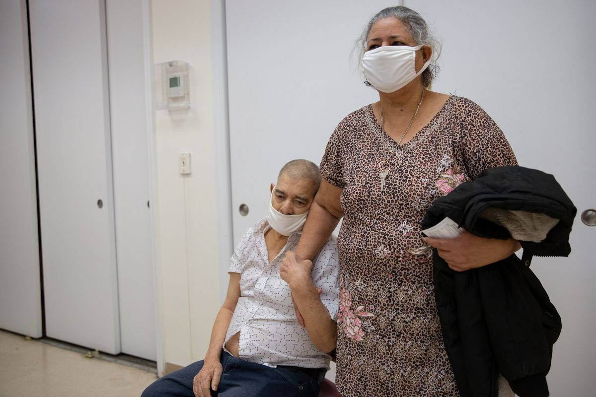 Wien House resident Bienvenido Vargas, who suffers from dementia, holds onto his wife, Belgica, after the couple received their second coronavirus vaccine, March 3, 2021.