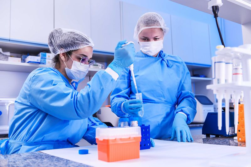 Two scientists in blue scrubs work in a medical lab.