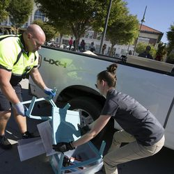 Salt Lake City police officer Lyman Smith and Karla Bartholomew, health scientist with the Salt Lake County Health Department, throw away the contents of encampments on 500 West on Wednesday, Sept. 28, 2016.