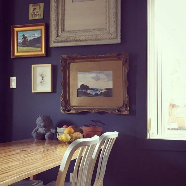 A navy wall hung with photos above a wooden table.