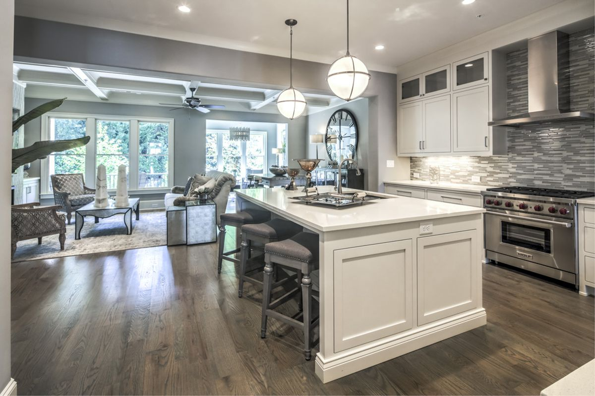 A high-ceilinged kitchen with white cabinets and dark wood floors.